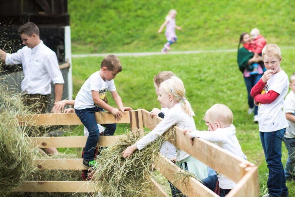 kindergruppe am permakulturhof ellersbacher bei spielen mit heu im hintergrund stefan schwaighofer der den kindern den hof zeigt und erklaert